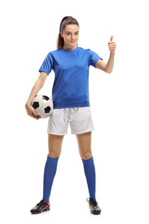 Full length portrait of a female soccer player making a thumb up sign isolated on white background