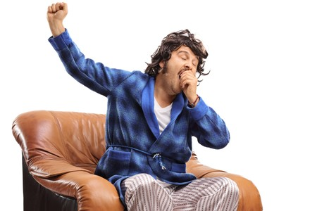 Sleepy man sitting in an armchair and yawning isolated on white background