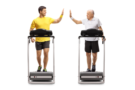 Full length profile shot of a young man and a senior walking on treadmills and high-fiving each other isolated on white background