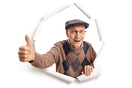 Cheerful senior breaking through paper and making a thumb up sign