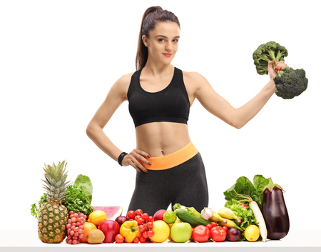 Fitness woman with a broccoli dumbbell behind a table with fruit and vegetables isolated on white background