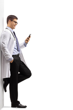 Full length profile shot of a doctor leaning against a wall and using a phone isolated on white background