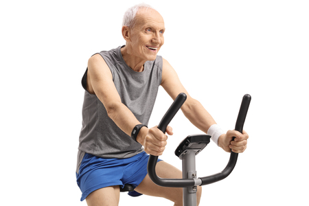 Senior working out on an exercise bike isolated on white background