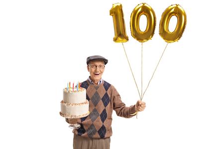 誕生日ケーキと白い背景に隔離された数百の風船を持つ幸せなシニア