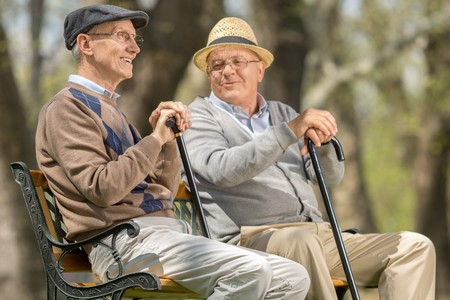 Two elderly men seated on a bench talking with each other outdoors