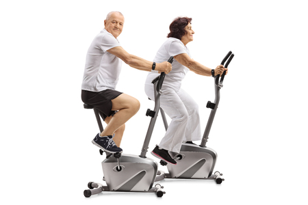 Mature man and a mature woman exercising on stationary bikes isolated on white background