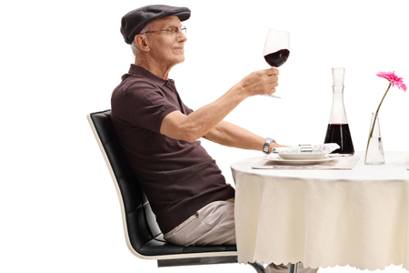 Senior seated at a restaurant table tasting red wine isolated on white background
