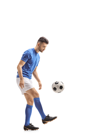Full length profile shot of a soccer player with a football isolated on white background