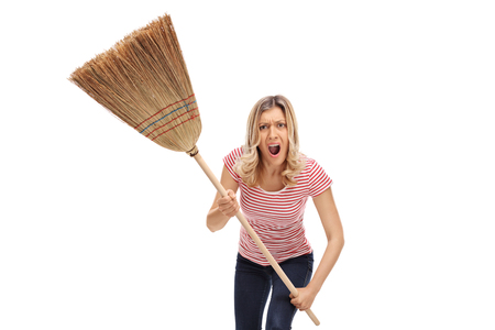 Angry young woman with a broom isolated on white background Banque d'images