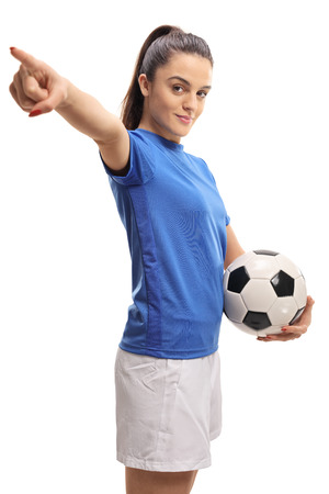 Female soccer player holding a football and pointing isolated on white background Stockfoto