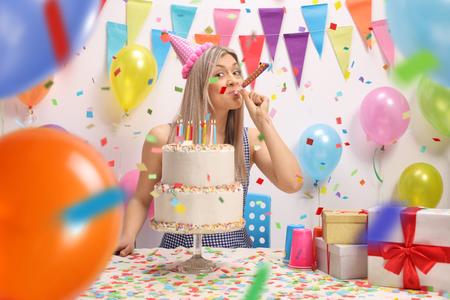 Mujer joven con un pastel de cumpleaños que sopla una bocina de fiesta contra una pared con globos y banderas de decoración Foto de archivo - 99480732