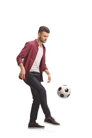 Full length profile shot of a young guy juggling a football isolated on white background Stock Photo