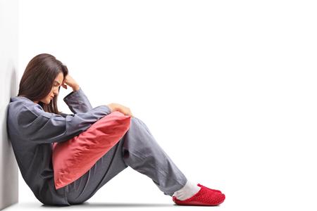 Triest jonge vrouw in pyjama zittend op de vloer en met een kussen geïsoleerd op een witte achtergrond