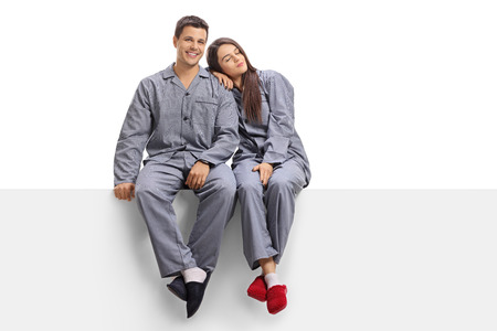 Young couple wearing pajamas sitting on a panel isolated on white background Banque d'images