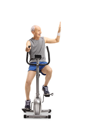 Senior exercising on a stationary bike making a high-five gesture isolated on white background Stock Photo