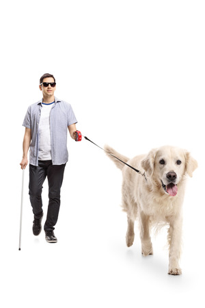 Full length portrait of a blind young man walking with the help of a dog isolated on white background