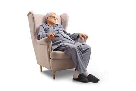 Mature man sleeping in an armchair isolated on white background