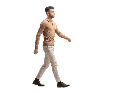Full length profile shot of a young man walking isolated on white background