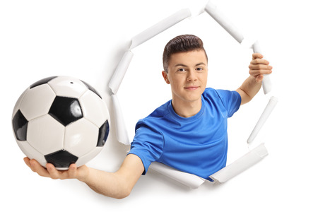Teenage soccer player showing a football and breaking through paper