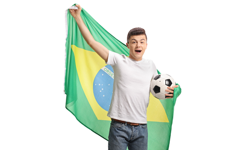 Joyful teenage soccer fan holding a football and a Brazilian flag isolated on white background