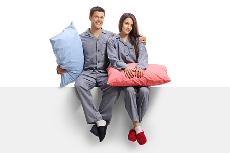 Young couple dressed in pajamas sitting on a panel and holding pillows isolated on white background