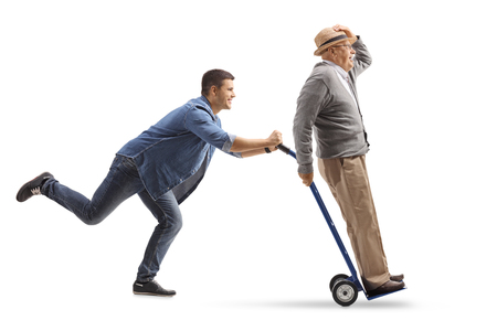 Full length profile shot of a young man pushing a hand truck with a mature man riding on it isolated on white background