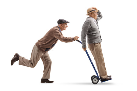 Full length profile shot of a senior pushing a hand truck with another senior riding on it isolated on white background