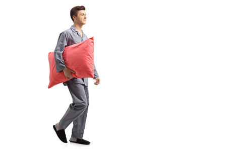 Full length profile shot of a teenage boy in pajamas holding a pillow and walking isolated on white background Stock Photo