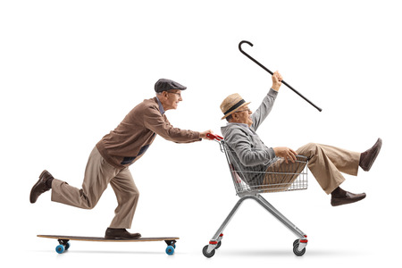 Senior riding a longboard and pushing a shopping cart with another senior riding inside it isolated on white background