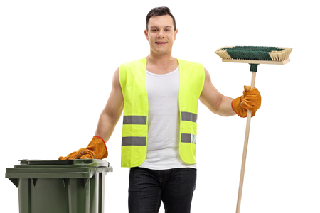 Waste collector holding a garbage bin and a broom isolated on white background 免版税图像