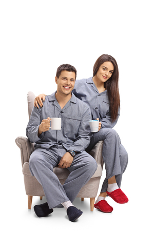 Young couple dressed in pajamas sitting in an armchair and holding cups isolated on white background Stock Photo