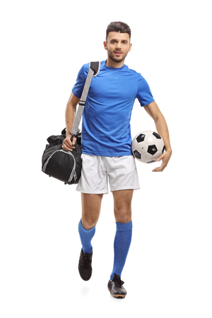 Full length portrait of a soccer player with a bag and a football walking towards the camera isolated on white background Archivio Fotografico