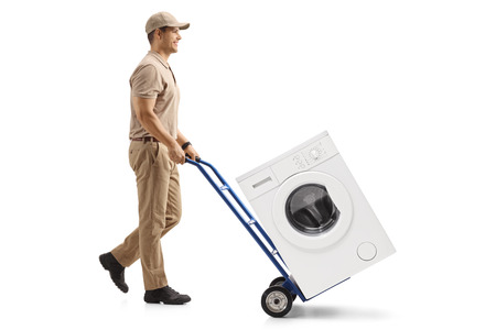 Full length profile shot of a delivery man pushing a hand truck loaded with a washing machine isolated on white background