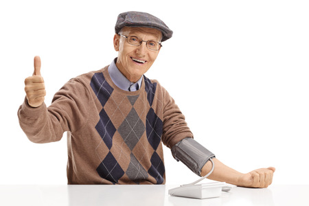 Senior seated at a table measuring his blood pressure and making a thumb up sign isolated on white background