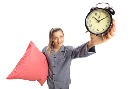 Young woman in pajamas holding a pillow and an alarm clock isolated on white background