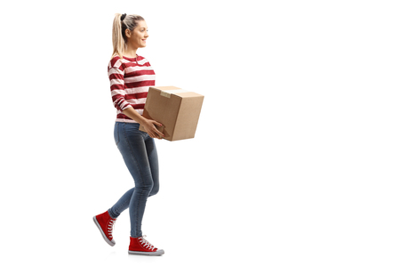 Full length profile shot of a young woman carrying a box and walking isolated on white background