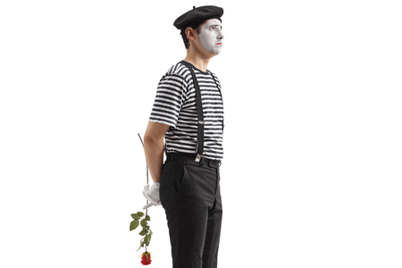 Sad mime holding a rose behind his back isolated on white background Foto de archivo