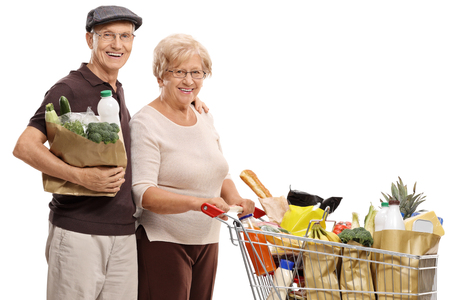 Senior couple with a shopping bag and a shopping cart isolated on white background