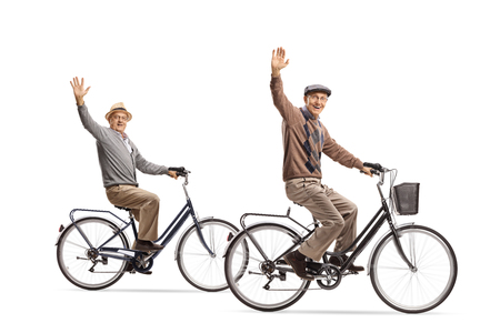 Seniors riding bicycles and waving at the camera isolated on white background