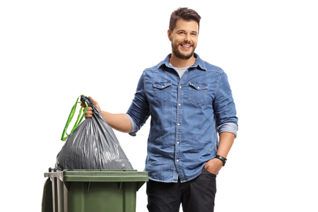 Jonge mens die het huisvuil neemt dat op witte achtergrond wordt geïsoleerd