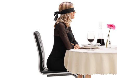 Young woman wearing a blindfold sitting at a restaurant table isolated on white background Standard-Bild