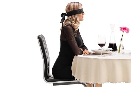 Jonge vrouw die een blinddoek draagt ?? die aan een restaurantlijst zit die op witte achtergrond wordt geïsoleerd