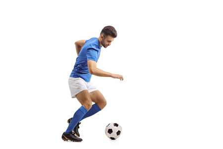 Full length profile shot of a soccer player dribbling isolated on white background Stock Photo