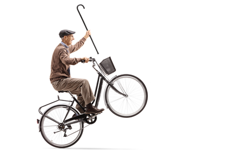 Joyful senior with a cane riding a bicycle and doing a wheelie isolated on white background