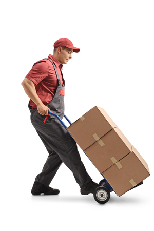 Full length profile shot of a mover with a hand truck loaded with cardboard boxes isolated on white background Stock Photo