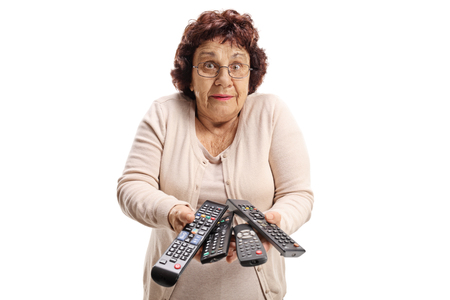 Confused elderly woman with remote controls isolated on white background Imagens