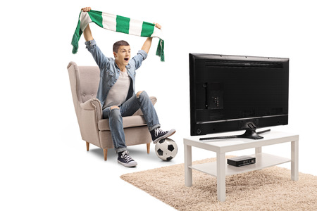 Overjoyed teenage soccer fan holding a scarf and watching a match on television isolated on white background