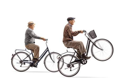 Seniors riding bicycles with one of them doing a wheelie isolated on white background Stock Photo