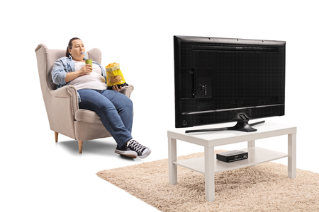 Overweight woman with a bag of chips and a drink sitting in an armchair and watching television isolated on white background