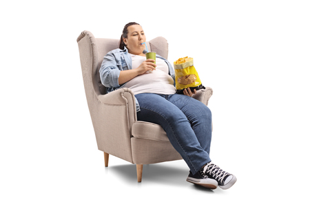 Overweight woman with a drink and a bag of chips sitting in an armchair isolated on white background